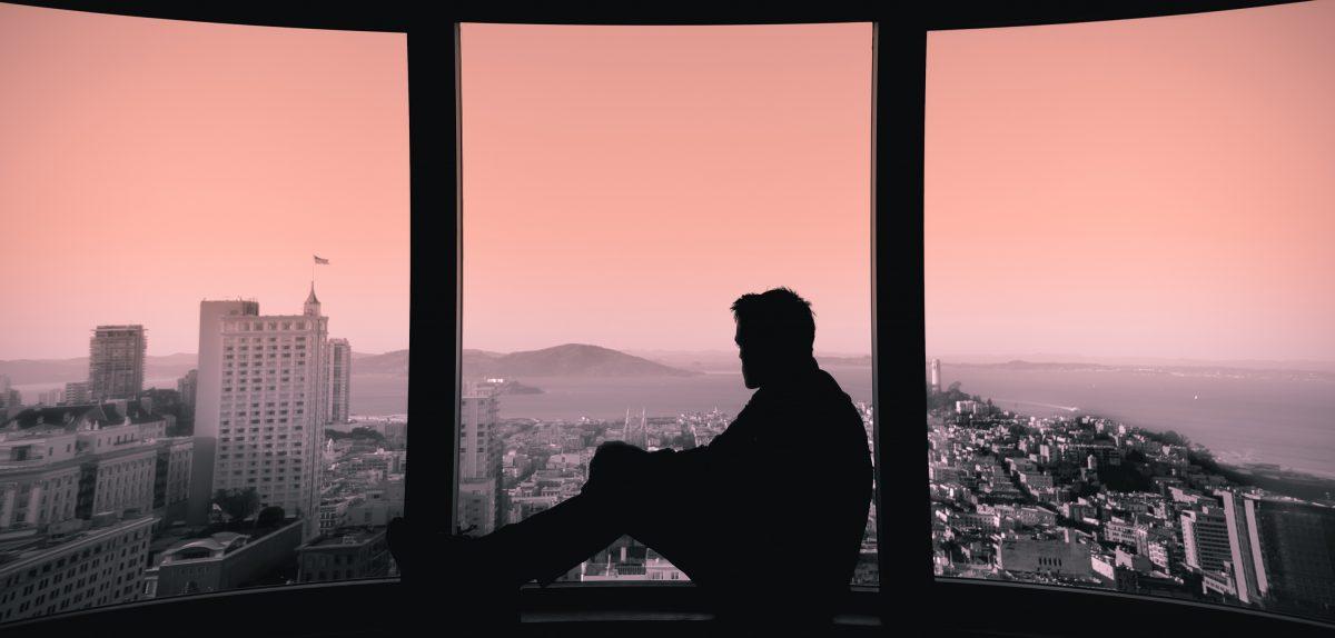 person sitting on windowsil, in the city, sunset