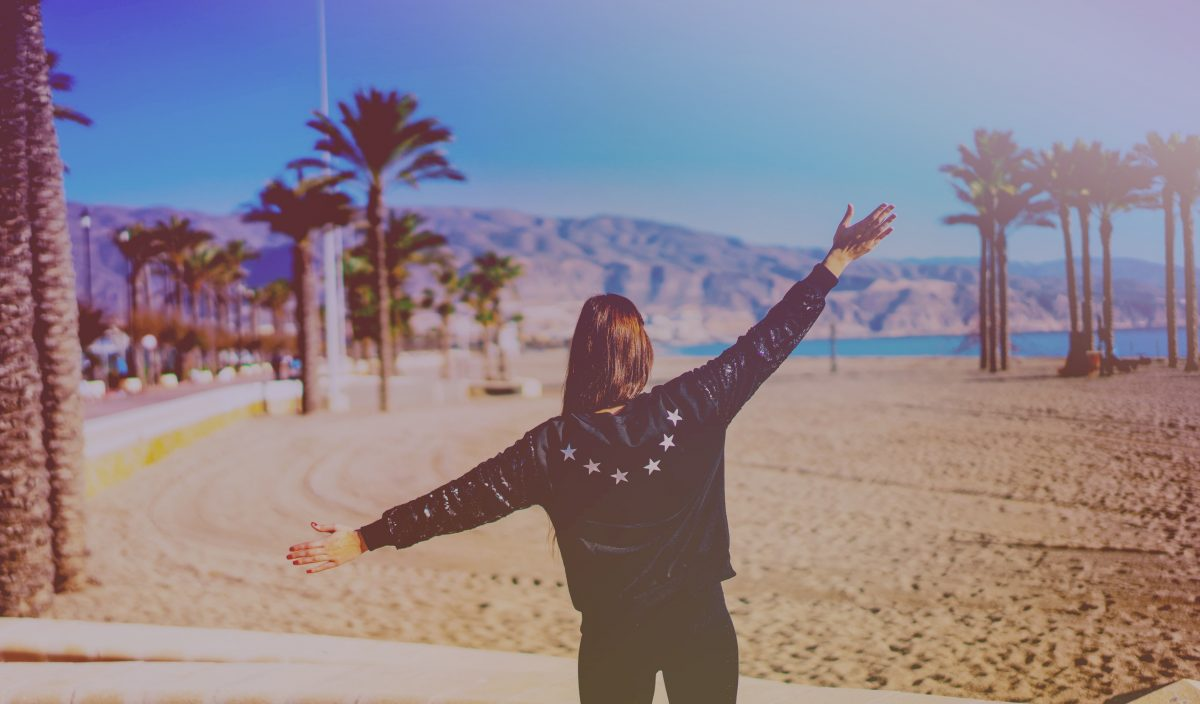 Girl on beach in leather jacket in summertime